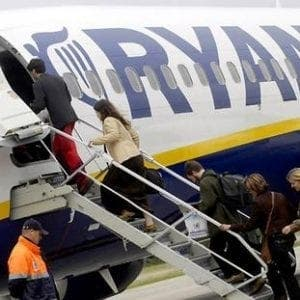 Ryanair passengers queue to board a flight.