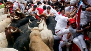 Runners get trapped with Fuente Ymbro fighting bulls during the seventh running of the bulls of the San Fermin festival in Pamplona