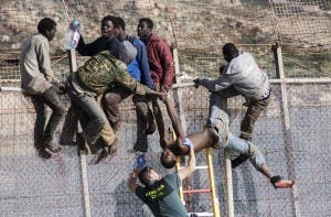 An African migrant is lowered from a border fence by a Spanish Civil Guard at the border between Morocco and Melilla during the latest attempt to cross into Spanish territory