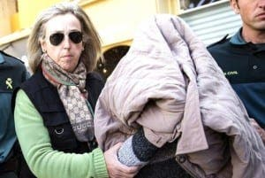 The accused covers her face after arrest in 2014