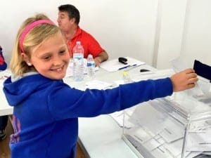 Maia Clarke, 10, helps her dad Jon, editor of the Olive Press vote this afternoon.