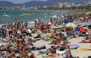Tourists crowd Palma de Mallorca's Arenal beach on the Spanish Balearic island of Mallorca July 25, 2011. Spain was host to 24.8 million foreign tourists in the first half of 2011, a 7.5% increase over the same period in 2010, according to figures from the Spanish Institute for Tourist Studies. REUTERS/Enrique Calvo (SPAIN - Tags: TRAVEL SOCIETY) - RTR2PA0I