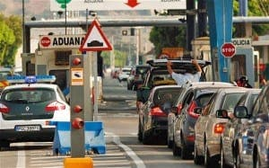 A Spanish civil guard conducts a check on a car while other drivers wait in line to enter to the British territory of Gibraltar at its border with Spain