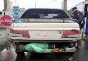 migrant in car bumper