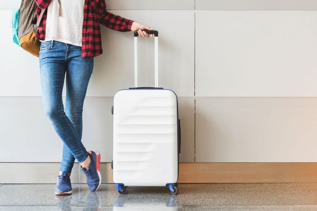 Woman Luggage Airport Shutterstock_683275162 1024x683