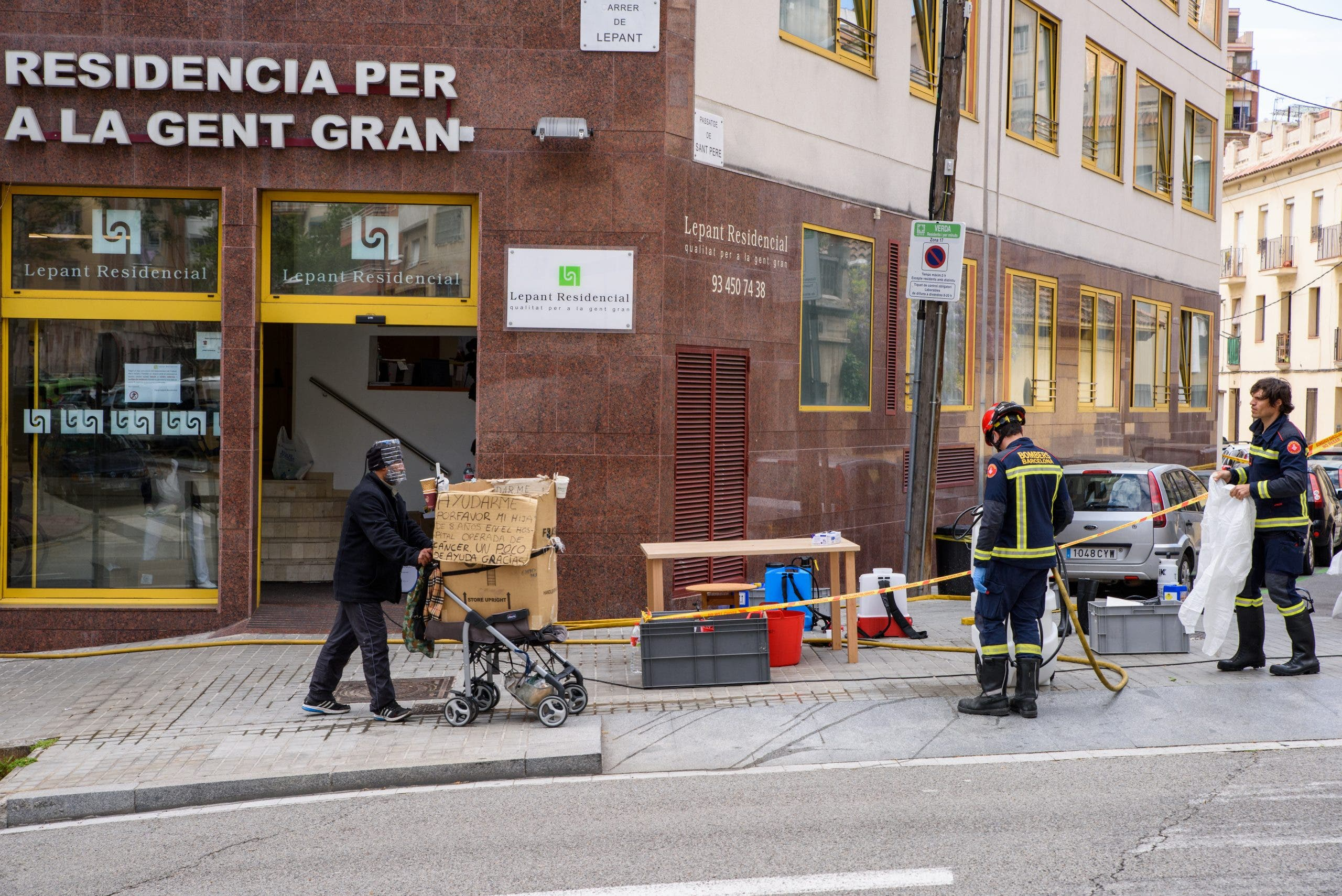 Homeless Man Walks Past Bomberos Preparing To Disinfect A Care Home 1