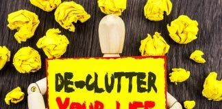 Announcement Text Showing De Clutter Your Life Concept Meaning Free Less Chaos Fresh Clean Routine Written On Sticky Note Holding By Sculpture On The Wooden Background