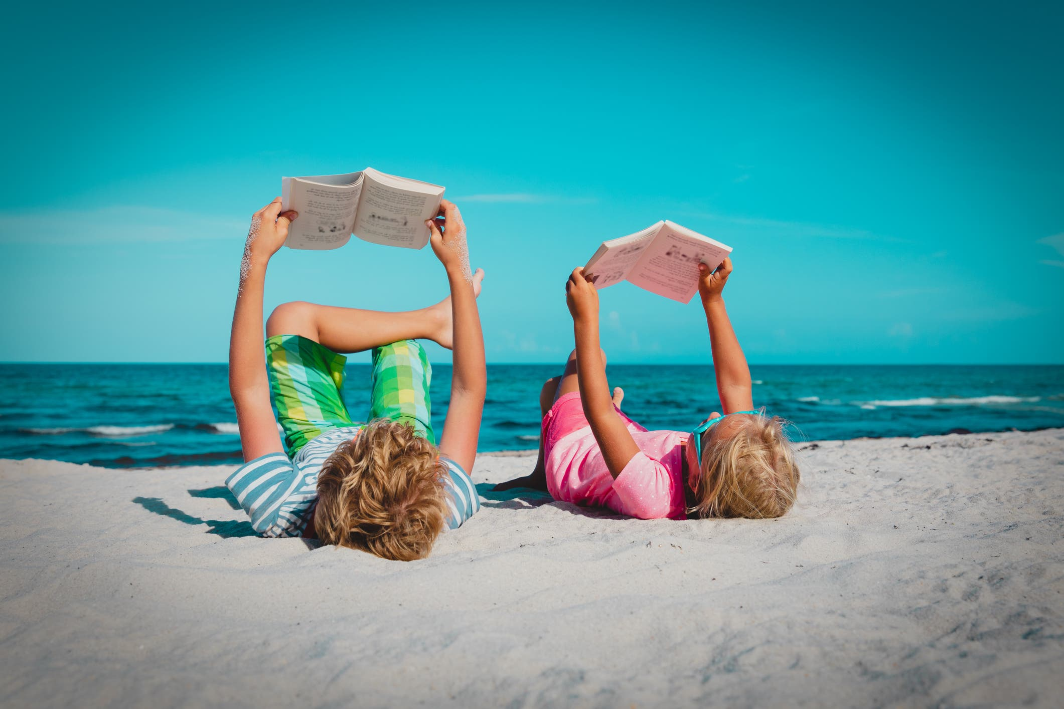 Boy And Girl Reading Books At Beach Vacation
