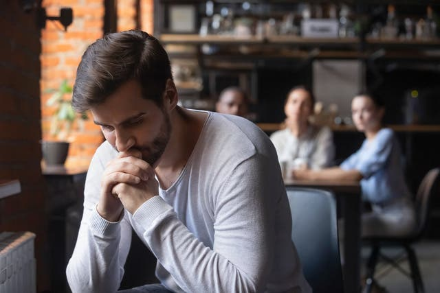 Sad Guy Sitting Alone Separately From Other Mates In Cafe