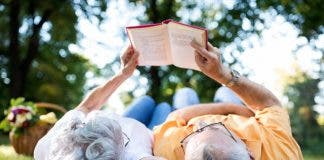 Senior Couple Resting At Park Reading A Book