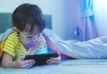 Cute Little Child Watch Movie On Smartphone At Bed Dangers Of Blue Light Can Damage Eyes Handsome Little Boy Can Be Age Related Macular Degeneration From Blue Light Wear Eyeglasses Since Childhood