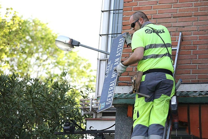 A council worker takes down a street plaque bearing the name of a fascist general